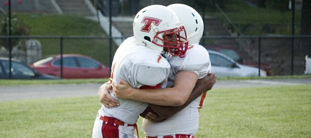 Tonganoxie High sophomore running back Cole Holloway is congratulated by lineman Gus Dent after scoring a first-quarter rushing touchdown Friday at Bishop Ward, in Kansas City, Kan. Holloway's score was the first of five rushing touchdowns for the Chieftains in a 34-6 victory.
