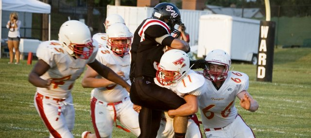 Tonganoxie High sophomore safety Joe Wolf lifts Bishop Ward running back Andrew Ramirez off the ground while making a first-quarter tackle Friday in the Chieftains' 34-6 win in Kansas City, Kan. The THS win came two days after 11-year coach Mark Elston resigned.