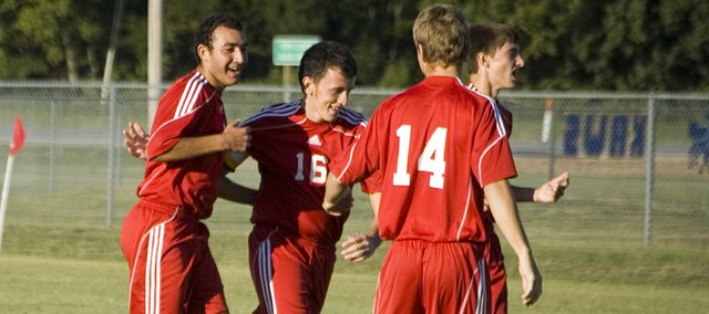 Joseph Parrino is congratulated by Tonganoxie High teammate Tyler Bartholomew after scoring a goal in the second minute at Perry-Lecompton on Thursday. The Chieftains won the road match, 2-0.