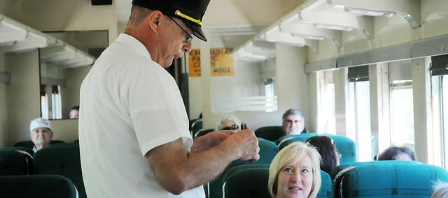 Miland Railway conductor Mark Mosley punches a ticket of one of the passengers attending Railfest. The Labor Day Weekend event celebrated the 60-year anniversary of two the railroad's locomotives and the 80-year anniversary of a postal car.