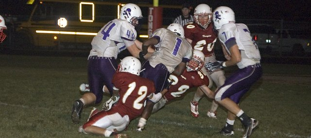 Tonganoxie High's Eric Tate (12) and Jared Somers (32) try to bring down Piper running back Matt McDonald Friday night in the Chieftians' 21-17 home loss to the Pirates.