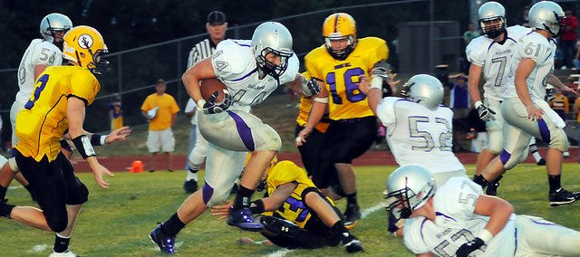 Baldwin High School junior Dayton Valentine, center, follows his blockers as he runs through Spring Hill defenders Friday night. Valentine's reception from junior Tyler Cawley netted 25 yards. BHS won the game 35-20.