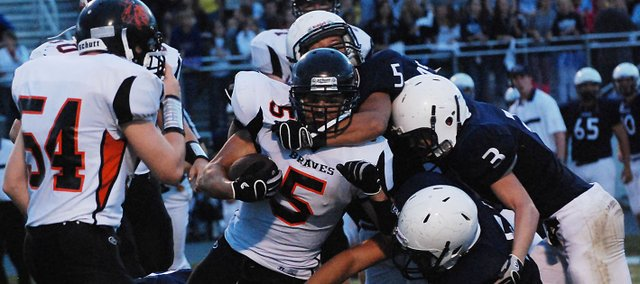 Bonner Springs running back J.J. Jackson runs into a wall of Mill Valley defenders including Justice Oehlert (3) and T. J. Phillips (5).