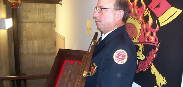 Tony Turner of Basehor, assistant chief and chaplain for the Fairmount Township Fire Department, holds a piece of steel from the World Trade Center towers that collapsed on Sept. 11, 2001, on Sunday in the first-floor stairwell of Town Pavilion in Kansas City, Mo. On Sunday, the 10th anniversary of the 9/11 attacks, 343 firefighters from six states scaled 110 flights of stairs in honor of the 343 New York firefighters who died in the towers, in the first-ever. As they began each trip up the 34-story building, the firefighters touched the piece of metal from the towers.