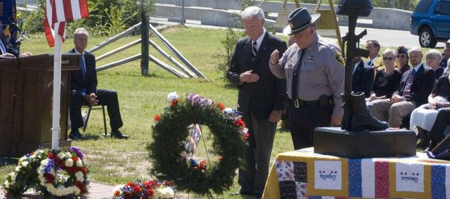 Leavenworth County Commissioner Clyde Graeber and Leavenworth County Sheriff Dave Zoellner pay their respects after participating in the laying of wreaths during Sunday's 9/11 remembrance ceremony at Leavenworth. Seated at left is U.S. Sen. Jerry Moran, R-Kan.