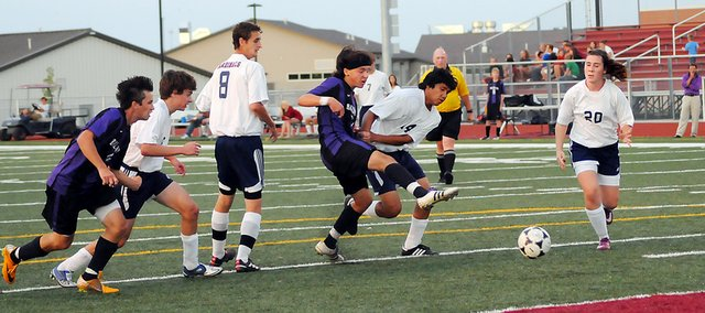 Baldwin High School sophomore Nick Joslyn, left, kicks a ball past two Eudora defenders Tuesday. Joslyn's kick resulted in the first goal of the game. BHS beat Eudora 2-0.