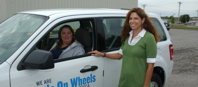 Paula Crook sits in the driver's seat of the new Ford Escape she will use to deliver meals to the homebound. Leavenworth County Council on Aging nutrition coordinator Julie Stark, right, secured $20,000 in grants from the Walmart Foundation and the Meals on Wheels Association of America, which paid for 90 percent of the Escape's cost.