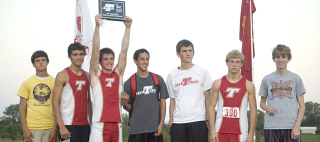 The Tonganoxie High boys cross country team takes the medal stand Tuesday following its first-place finish at the Tonganoxie Invitational. Pictured are, from left, Clayton Himpel, Dalton Harrington, Patrick Rachford, Caleb Himpel, Jeff Neal, Asher Huseman and Brady Field.
