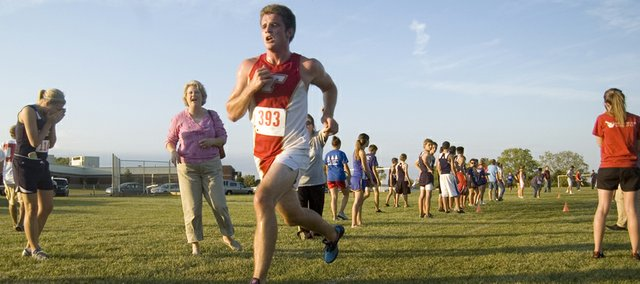 Tonganoxie High senior Patrick Rachford sprints toward a first-place finish Tuesday at the Tonganoxie Invitational as spectators cheer him on. Rachford's time of 16:25 was a personal record and helped the THS boys win a team title.