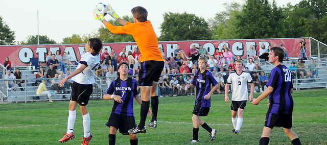 Baldwin High School junior goalkeeper Mason Bandré snags a ball over an Ottawa player's head after a Cyclones' player booted a corner kick. Bandré helped the Bulldogs beat Ottawa 2-0.