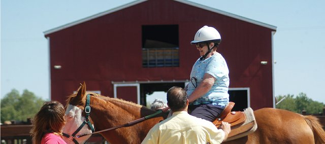 Danila Rock enjoys her first horseback ride in more than 50 years at New Horizon Ranch in Rantoul. Ranch volunteer Lynn Riddle, Shawnee, and CEO Brian Miller help guide her atop a 15-year-old gelding named Tooie. On Sept. 20 a wish-granting group enabled Rock, an 85-year-old resident at Sweet Life Shawnee, to ride a horse for the first time since she emigrated from Italy, where she rode daily in her youth.