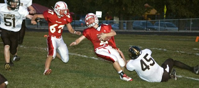 Tonganoxie High quarterback Garret Elston is dragged to the ground by Turner's Drake Leger Friday night in a 36-6 home loss.