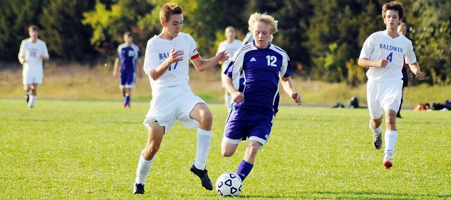 Baldwin High School senior Clint Chapman battles Spring Hill's Spencer Hart during the second half of Tuesday's game. The Bulldogs won the game 2-1, avenging one of their two losses this season.