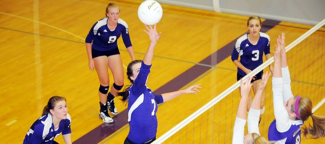 Baldwin High School senior Madeline Brungardt tips a ball over two Louisburg defenders Tuesday evening. The Bulldogs fell to the Wildcats in three sets. Baldwin returns to action Saturday at the Wellsville Tournament. BHS will host its Dig Pink night on Tuesday to raise money for Breast Cancer research.