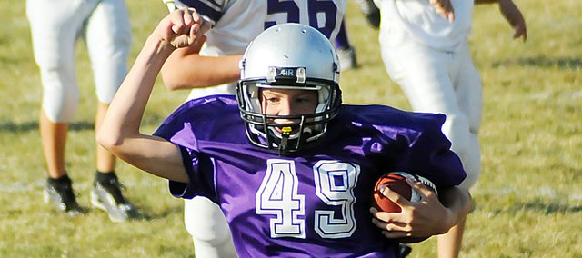 Baldwin Junior High School eighth-grader Cole Wolff celebrates after scoring a touchdown on an interception return. Wolff ran nearly 50 yards to score after catching the interception. He helped the Bulldogs beat Louisburg 16-12 and remain unbeaten at 5-0.