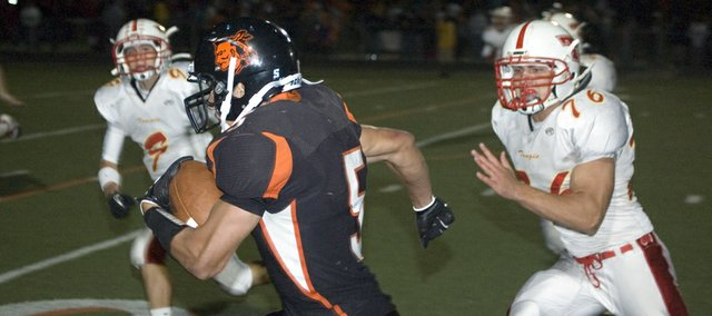 Bonner Springs High senior running back JJ Jackson runs down the sideline for one of his five rushing touchdowns  as Tonganoxie's Tyler Ford and Jonas Myers try to track him down Friday at David Jaynes Stadium. The Braves defeated THS, 48-13.