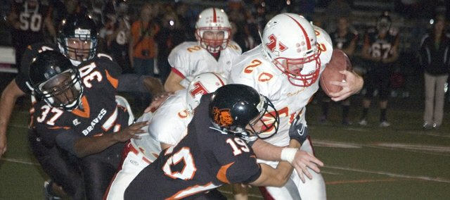 Tonganoxie High senior running back Derek Lingo tries to stay upright with Bonner Springs defensive back Jonathan Blackwell hanging on him Friday at David Jaynes Stadium. The Chieftains lost at BSHS, 48-13.