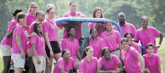 Kansas  women's basketball coach Bonnie Henrickson, left, and the KU women's basketball team, decked out in pink shirts, poses at the start of Henrickson's annual charity golf tournament in Lawrence. Proceeds from the event benefit breast cancer research. October is National Breast Cancer Awareness Month.