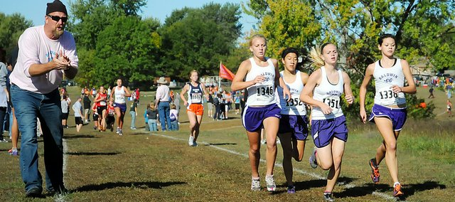 Baldwin High School cross country coach Mike Spielman, left, cheers on a pack of four Bulldogs during the girls' 4-kilometer race Saturday morning at the Baldwin City Municipal Golf Course. The Bulldogs, from left, are senior Elizabeth Sigvaldson, junior Elena Watson, sophomore Libby Verhaeghe and sophomore HannahHutton. BHS placed third as a team.