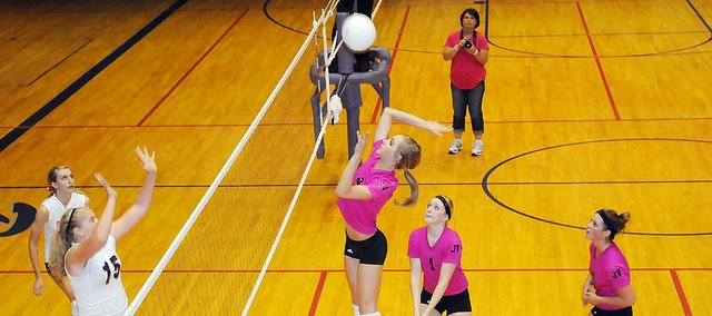 Baldwin High School sophomore Morgan Lober, center, spikes the ball during the second set of the Bulldogs home match against rival Eudora. The Bulldogs beat Eudora in five sets, winning their first Frontier League match. It was also Dig Pink Night at BHS as the team and fans wore pink to raise money for Breast Cancer research.