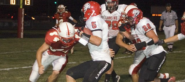 Tonganoxie High senior defensive lineman Dallas Jacobs lunges forward at Lansing quarterback Litton VanDerWerff in the first quarter of the Chieftains' 37-7 homecoming loss Friday at Beatty Field.