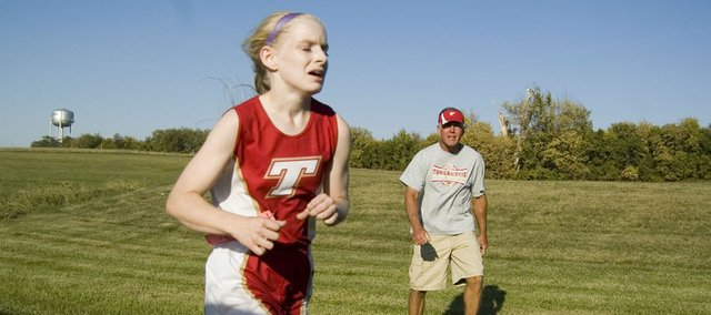 Halston Field runs Thursday at the Pleasant Ridge Invitational as Tonganoxie coach Phil Williams encourages her.