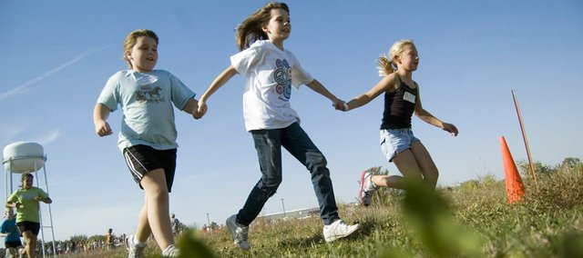 Tonganoxie Elementary School students Sydney Angell, Meghan Agnew and Abbigayle Hefton take it easy Wednesday at the annual Tonganoxie Kids Cross Country Race and hold hands as they go.