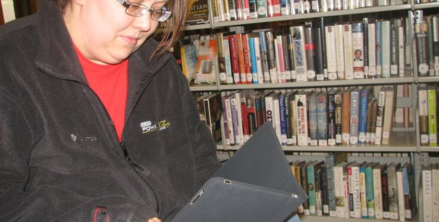 Jennifer Bleam, a Friends of the Basehor Community Library member, tries reading an e-book on an iPad she borrowed as part of the library&#39;s Digital Readers group. She said the bountiful games available for the device had distracted her from getting much reading done, but she looked forward to trying out simpler e-readers such as the Kindle and the Nook.