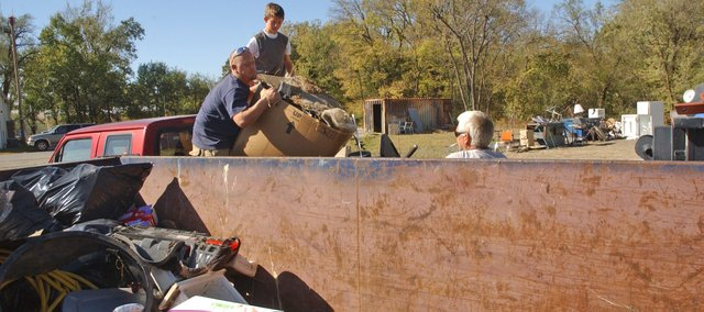 Jesse Dohle, Andrew Ray and Troy Morton unload a pickup of trash Saturday during the Tonganoxie citywide cleanup in the last of seven roll-off containers filled during the successful event.