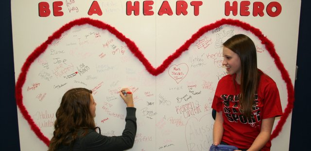 "Basehor-Linwood High School student Danielle Ridder (left) signs her name to the school's ""Heart Hero"" board as Caylea Siler, a member of the school's Family, Career and Community Leaders of America chapter, watches on. The board will be on display at the football game Friday against Tonganoxie."