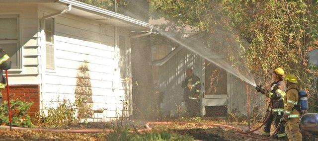 A firefighter with the city of Tonganoxie Fire Department sprays down the south side of a house Thursday at 905 Delaware Street after a fire, which apparently started in a compost pile, threatened that house and one to the south.