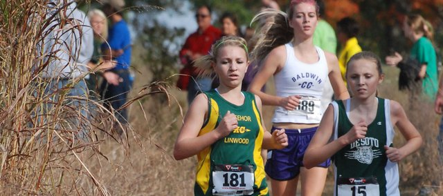 Basehor-Linwood freshman Quinnlyn Walcott battles a De Soto runner for positioning late in the Class 4A regional race at Wyandotte County Park. Walcott finished fourth overall and qualified for state.