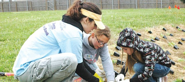 Kate Becker, program manager for Keeping Kansas City Beautiful, walks fourth graders Maggie Dewsberry and Olivia Ducey through planting one of nine species of plants in the newly-installed rain garden at Bluejacket-Flint Elementary School on Saturday, May 14. The rain garden is a model for the organization, which hopes to install 10,000 around the Kansas City metro area.