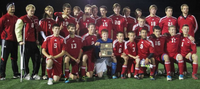 The Tonganoxie boys soccer team celebrates with its Class 4-1A regional championship plaque.