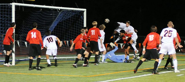 Baker University's Odaine Sinclair, center, heads a ball into net to score the Wildcats' third goal Saturday night at Liston Stadium. Baker beat rival Benedictine 3-0 and is now ranked No. 2 in the NAIA.