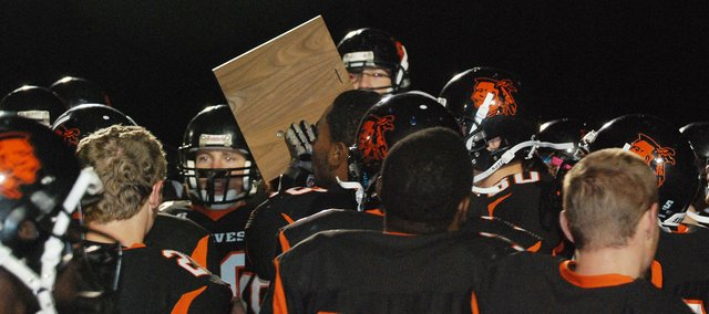 The Bonner Springs Braves hoist the Class 5A District 1 championship plaque after beating Lansing 35-21.