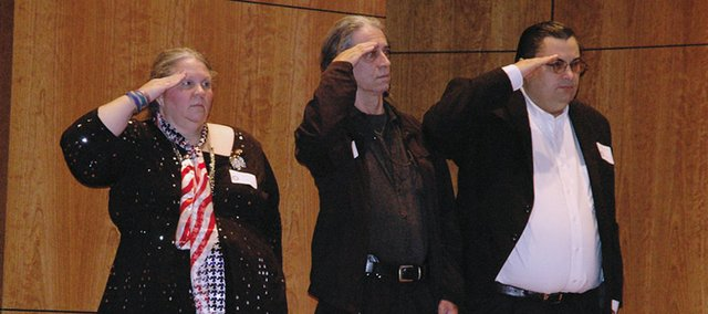 U.S. military veterans, who were speakers at the Veterans' Pen Celebration Saturday, Oct. 29, salute the American flag during the celebration. Pictured from left are Leah Ann Jones of Kansas City, Kan., David Harrington of Kansas City, Kan., and Allen Yoakum of Liberty, Mo.