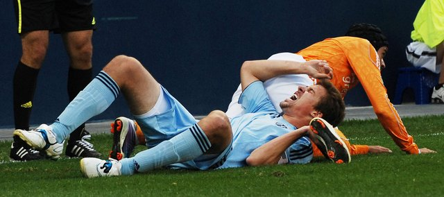 Sporting Kansas City defender Matt Besler grimaces in pain after being tackled by Houston&#39;s Calen Carr. Carr received a yellow card for a reckless tackle on the play.