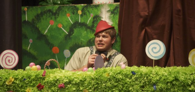 "Augustus Gloop, portrayed by Basehor-Linwood High School senior Trevor Hickman, cowers after being discovered eating from a river of chocolate during a rehearsal Tuesday night for ""Willy Wonka and the Chocolate Factory,"" this year's BLHS musical."