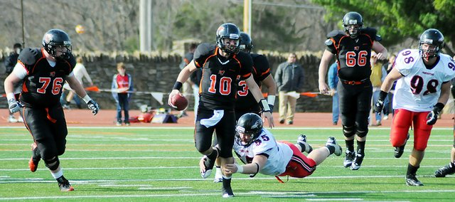 Baker University quarterback Jake Morse (No. 10) escapes a Benedictine defender as he scrambles for a gain. Morse completed 14 of 28 passes for 150 yards in Bakers 10-7 victory Saturday.