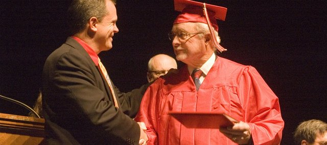 Galen Freeman, right, receives an honorary diploma from his alma mater Thursday at the Tonganoxie Performing Arts Center. Tonganoxie High School principal Jamie Carlisle presented Freeman with a diploma as part of a surprise ceremony. Freeman never finished high school at THS because he joined the Navy midway through his junior year in February 1946.