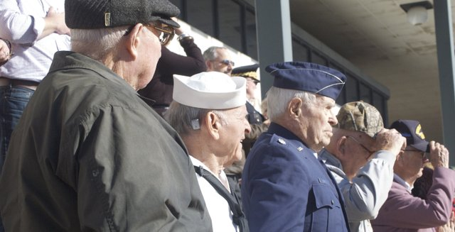 World War II veterans, at the reviewing stand at the Leavenworth County Veterans Day Parade, stand after saluting a color guard in the parade in downtown Leavenworth on Friday, Nov. 11. Pictured are, from left, retired Army Lt. Col. Harry Davis of Leavenworth; retired Army Col. B.B. Albert Jr. of Parkville, Mo. (who served in the Navy during WWII); and retired Air Force Lt. Col. Bill Adams of rural Leavenworth. Many parade participants stopped in front of the stand to thank the veterans there for their service.