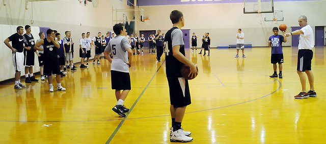 Baldwin High School boys' basketball coach Dustin Leochner, far right, talks to his players Tuesday at practice. The Bulldogs started the season Monday.