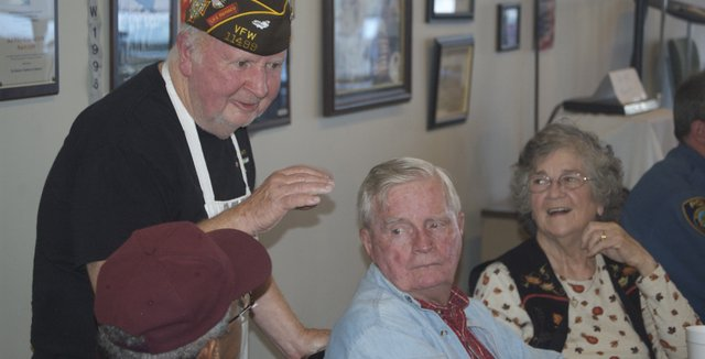 Richard Painter, a Basehor VFW Post member who served in the Navy during the Vietnam War, stops serving food to chat with, from left, Horace Lindesay of Kansas City, Mo., and Jack and Jeanette Rice of Kansas City, Kan.