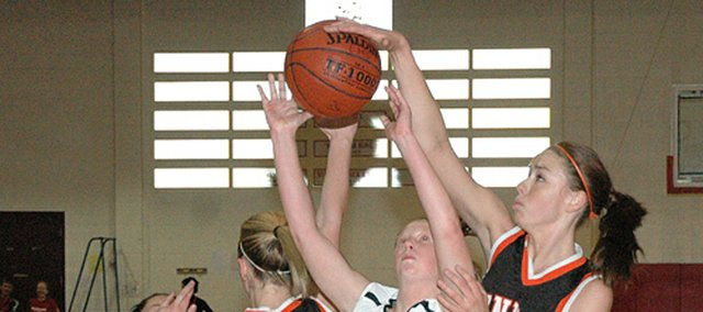 Christina Delladio, right, blocks a shot by Lansing's Amy Briggs during a game while Delladio was a student at Bonner Springs High School. Delladio earned a basketball scholarship to Baker University, but she eventually switched sports and played volleyball at BU.