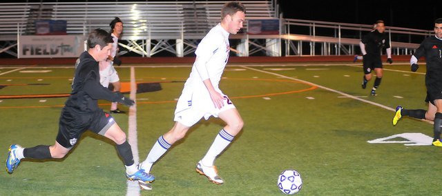 Baker University's senior Sean McAlister dribbles past an Oklahoma Wesleyan defender during the first half Saturday. Baker won the game 2-0, advancing to the NAIA championship round of 16, which starts Monday in Alabama.