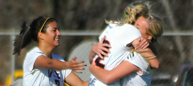 Members of the Baker University women's soccer hug each other after the opening goal Saturday. They are, from left, Ashley Sampson, Skylar Baker and Alix Schiraldi. Baker scored the goal for the Wildcats, who beat Bellevue (Neb.)  by the score of 2-1.