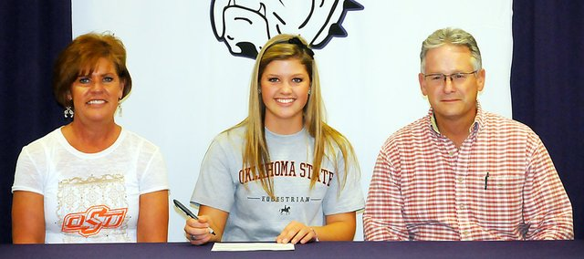Baldwin High School senior Paris Nottingham, center, signed a letter of intent last Thursday to join the equestrian team at Oklahoma State University. She is seated with her parents, Jeanne and David Nottingham.