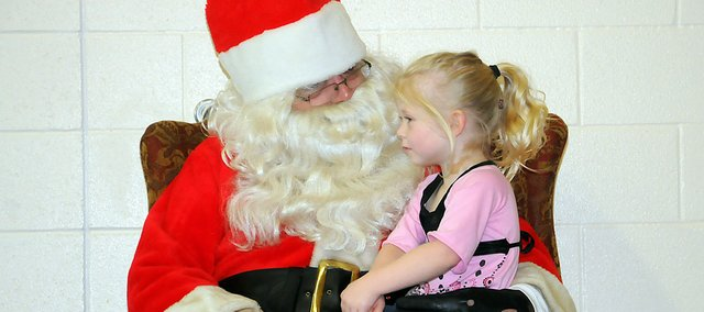 Addison Gardner, 4, of Wellsville sits on the lap of Santa Clause (Gary Browne) Saturday during the Baldwin City Recreation Commission's Breakfast with Santa at the Baldwin Elementary School Intermediate Center.