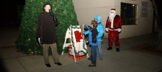 Tonganoxie Mayor Jason Ward finishes counting down to the lighting of the Mayor's Christmas Tree as Tonganoxie Elementary School fourth-graders Jakob Edhome and Alex Hartpence pull the switch. The two students were selected for the event and their ride with Santa Claus (Tom Putthoff, right) because of their grades and record of helping at school.